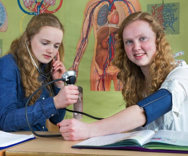 Two teenage girls measuring blood pressure in biology lesson