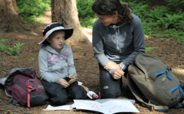 Small child with adult reading book in forest